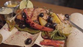 Pedazo de carne jugoso delicioso fresco con los vegetbles cerca para arriba Carne sabrosa que miente en la placa con maíz, salsas metrajes