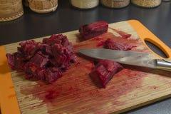 Pedazo de carne y de cuchillo en tabla de cortar Imagenes de archivo