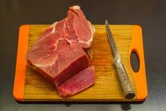 Pedazo de carne y de cuchillo en tabla de cortar Imagen de archivo