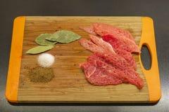 Pedazo de carne y sal y especias en tabla de cortar Fotos de archivo libres de regalías
