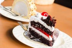 Pedazo de chocolate poner crema blanco de la torta en la cafetería Foto de archivo libre de regalías