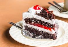 Pedazo de chocolate poner crema blanco de la torta en la cafetería Imágenes de archivo libres de regalías