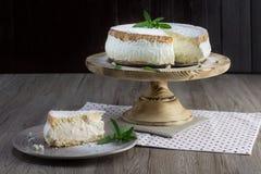 Pedazo de Crema-pastel de queso austríaco tradicional Käsesahnetorte del postre en una placa de madera imagen de archivo