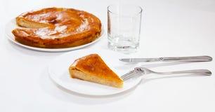 Pedazo de empanada de la cebolla con la fork y cuchillo y vidrio Imágenes de archivo libres de regalías
