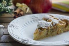Pedazo de empanada de manzana en una placa blanca elegante, fondo de madera Fotos de archivo