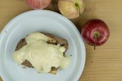 Pedazo de empanada de manzana con la salsa de la vainilla en el top imagen de archivo