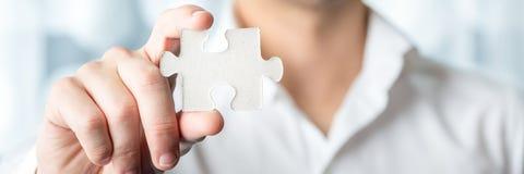 Pedazo de Holding Jigsaw Puzzle del hombre de negocios Fotos de archivo libres de regalías