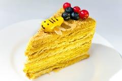 Pedazo de la torta de miel adornada con una abeja de Fotos de archivo libres de regalías