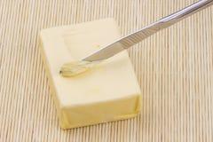 Pedazo de mantequilla y de cuchillo imagenes de archivo
