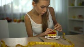 Pedazo de medición de torta con la cinta, miedo de la muchacha de ganar el peso, restricción de la comida metrajes