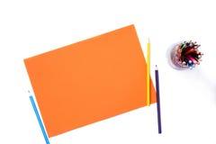 Pedazo de papel anaranjado con los lápices coloridos en fondo blanco aislado Fotografía de archivo