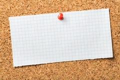 Pedazo de papel cuadriculado en blanco fijado a un corcho imagen de archivo