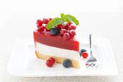 Pedazo de pastel de queso con la jalea de la fresa en una placa Fotos de archivo libres de regalías