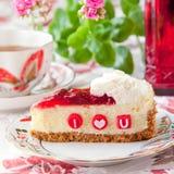 Pedazo de pastel de queso de la fresa con las letras comestibles para la tarjeta del día de San Valentín Fotos de archivo libres de regalías