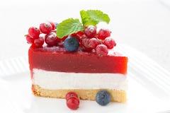 Pedazo de pastel de queso delicioso con la jalea de la baya en una placa blanca Fotografía de archivo libre de regalías