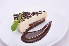 Pedazo de pastel de queso apetitoso con los microprocesadores de chocolate en una placa blanca foto de archivo