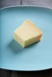 Pedazo de queso en la placa azul Foto de archivo libre de regalías