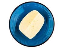 Pedazo de queso en la placa azul aislada en blanco Fotografía de archivo