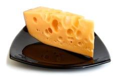 Pedazo de queso en la placa negra Fotografía de archivo