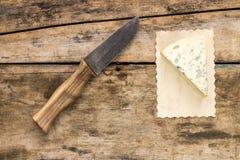 Pedazo de queso verde con el cuchillo en el fondo de madera Fotos de archivo libres de regalías