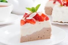pedazo de torta con crema, las fresas y el té azotados Imagen de archivo libre de regalías