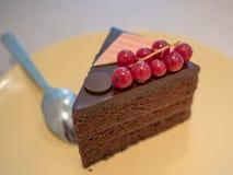 Pedazo de torta de chocolate en un plato amarillo en la tabla del café Foto de archivo