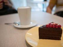 Pedazo de torta de chocolate en un plato amarillo en la tabla del café Foto de archivo libre de regalías