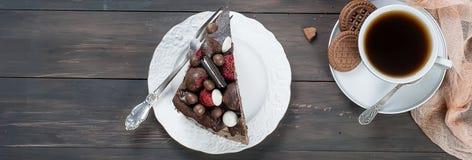 Pedazo de torta de chocolate en una placa y una taza de café Foto de archivo libre de regalías