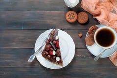 Pedazo de torta de chocolate en una placa y una taza de café Imagen de archivo libre de regalías