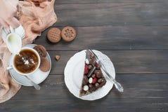 Pedazo de torta de chocolate en una placa y una taza de café Imagen de archivo
