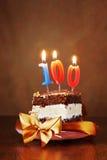 Pedazo de torta de cumpleaños con la vela ardiente como número ciento Fotografía de archivo libre de regalías