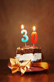 Pedazo de torta de cumpleaños con la vela ardiente como número treinta Imagen de archivo