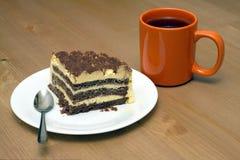 Pedazo de torta de esponja en una placa y una taza de primer del té Imagen de archivo