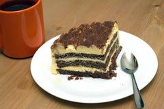 Pedazo de torta de esponja en una placa y una taza de primer del té Foto de archivo