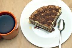 Pedazo de torta de esponja en una placa y una taza de primer del té Fotos de archivo