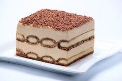 Pedazo de torta del tiramisu en la placa blanca Fotografía de archivo
