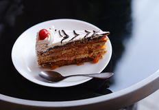 Pedazo de torta en la placa blanca en los wi negros de la tabla Fotos de archivo