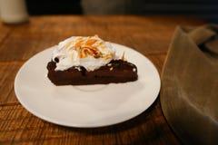 Pedazo de torta en la placa y la pañería del pantano en la tabla en café Foto de archivo