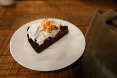 Pedazo de torta en la placa y la pañería del pantano en la tabla en café Fotografía de archivo