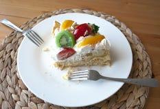 Pedazo de torta gigante en el plato blanco con 2 cucharas del té fotografía de archivo