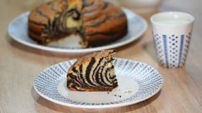 Pedazo de torta de la `` cebra `` con el esmalte del chocolate Coma la cebra de la torta almacen de metraje de vídeo