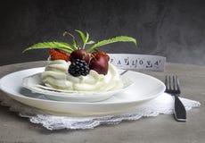 Pedazo de torta Pavlova del merengue con la crema azotada y la fresa fresca, zarzamora, cereza, pasa, menta fotografía de archivo