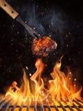 Pedazo del pollo en la parrilla con las llamas fotografía de archivo