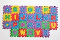 Pedazo del rompecabezas del alfabeto en el fondo blanco Imagen de archivo libre de regalías