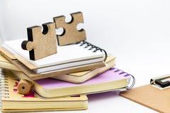 Pedazo del rompecabezas en la pila de libros, uso de la imagen para solucionar los problemas, concepto del fondo de la educación fotografía de archivo