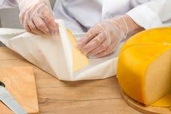 Pedazo envuelto manos de queso en papel fotografía de archivo libre de regalías