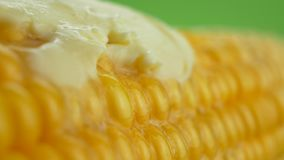Pedazo fresco sabroso de mantequilla que derrite en maíz fresco amarillo maduro en mazorcas metrajes
