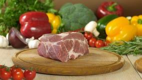 Pedazo grande de carne cruda en un fondo de verduras en un tablero de madera foto de archivo