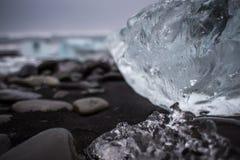 pedazo grande de hielo en una playa negra Foto de archivo libre de regalías