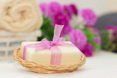 Pedazo grande de jabón beige en el busket, arco púrpura del witn, flores en b Imagen de archivo libre de regalías